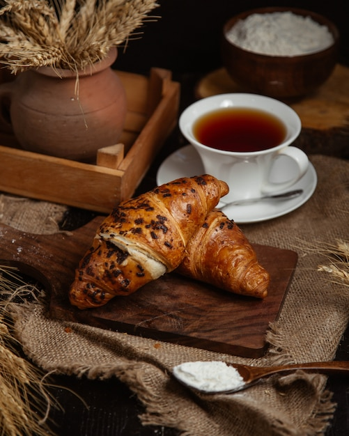 French croissants with a cup of black tea. Free Photo