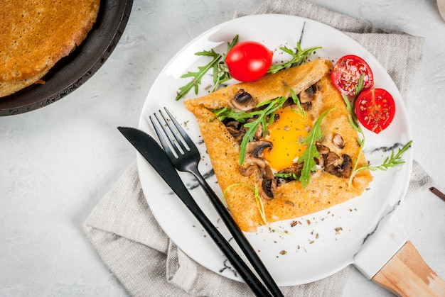 French cuisine breakfast lunch snacks vegan food traditional dish galette sarrasin crepes with eggs cheese fried mushrooms arugula leaves and tomatoes Premium Photo
