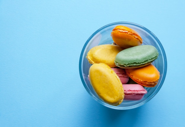 French dessert multicolored macaroni on blue background Premium Photo