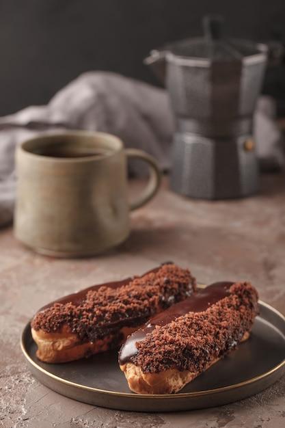 Французские эклеры. шоколадно-сливочные эклеры к кофе. сладости на кофе-брейк Premium Фотографии