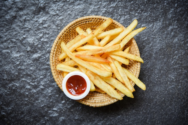French fries on basket with ketchup on dark Premium Photo