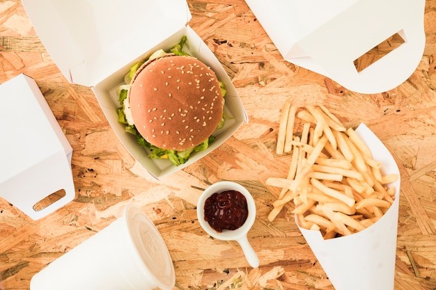 French fries; burger and french fries on wooden texted background Free Photo