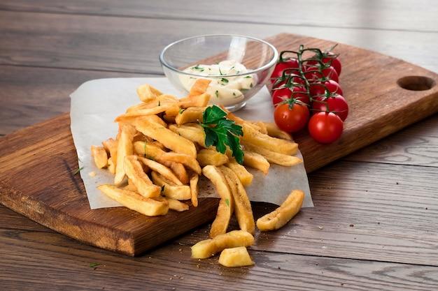 French fries, cherry tomatoes, garlic sauce on wood Premium Photo