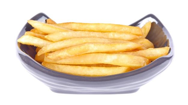 Картофель фри в черной миске на белой поверхности Premium Фотографии