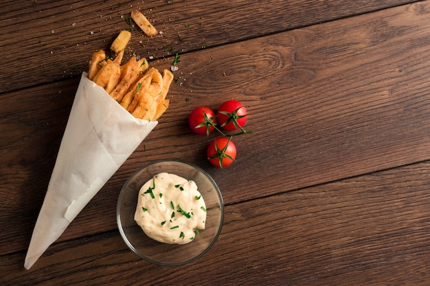 French fries, in a paper bag on wood Premium Photo