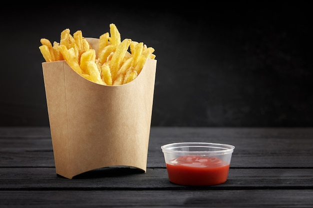 French fries in a paper basket. fast food.french fries in a paper box on black space Premium Photo