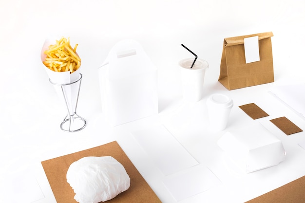 French fries; parcel; burger and disposable cup mockup on white background Free Photo