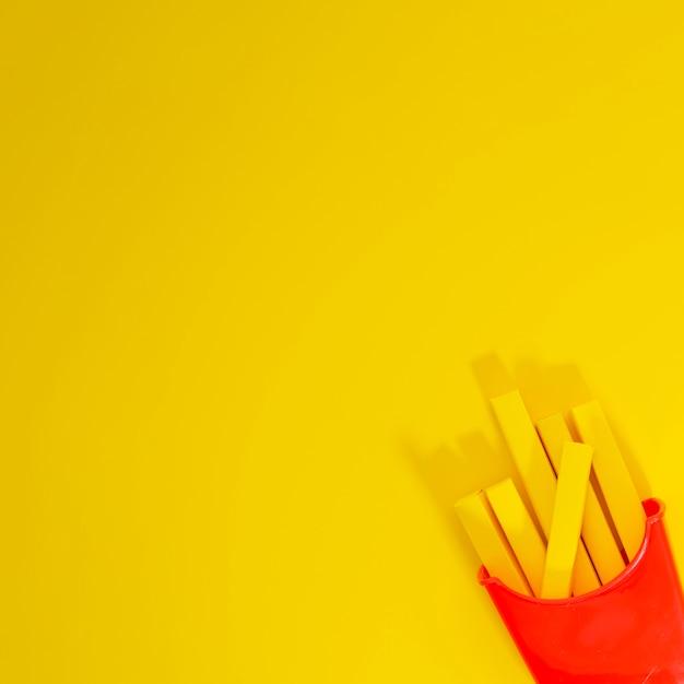 Картофель фри реплики на желтом фоне Бесплатные Фотографии
