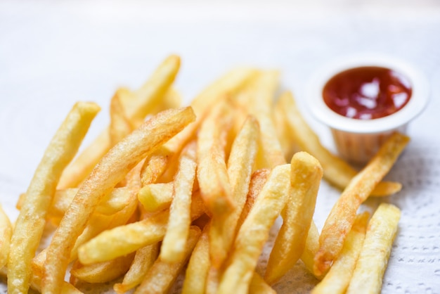 French fries on white paper with ketchup on dining table Premium Photo