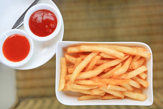 French fries on white plate serve with chili and tomato sauce on table. above view. Premium Photo