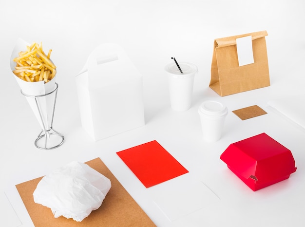 French fries with food packages and disposal cup on white backdrop Free Photo
