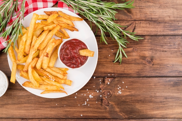 French fries with yummy ketchup on wooden table Free Photo