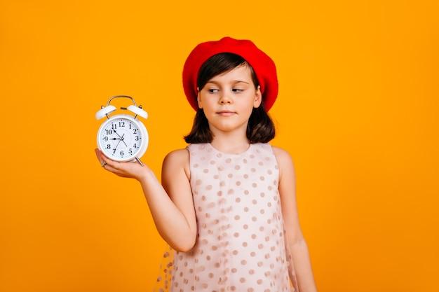 Ragazzo francese in berretto alla moda. bambino caucasico che propone sulla parete gialla con l'orologio. Foto Gratuite