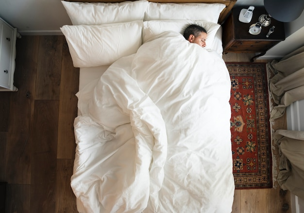 French man sleeping alone on bed Premium Photo