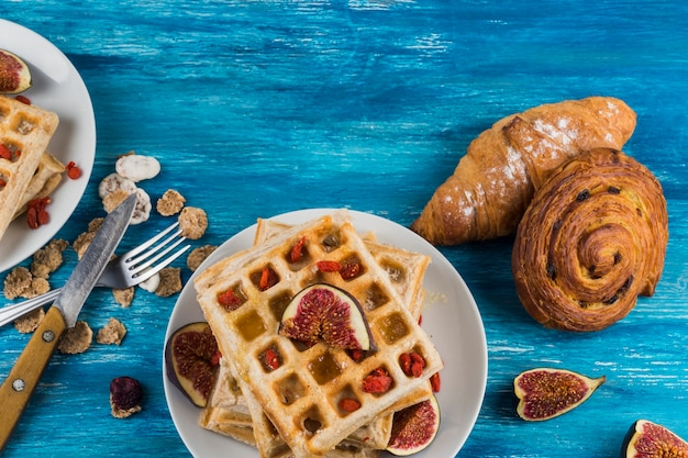 French pastries; corn flakes and waffles on fig over the wooden background Free Photo
