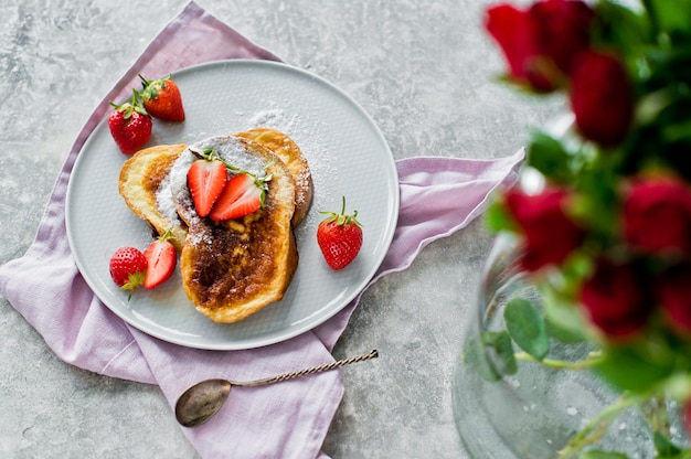 French toast with strawberries. vase with roses. Premium Photo