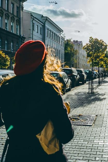 ベレットの通りにバゲットを持つフランス人女性 無料写真