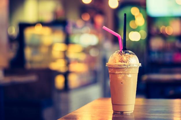 コーヒーショップでぼやけた背景の木製テーブルにコーヒーやココアfreppe Premium写真