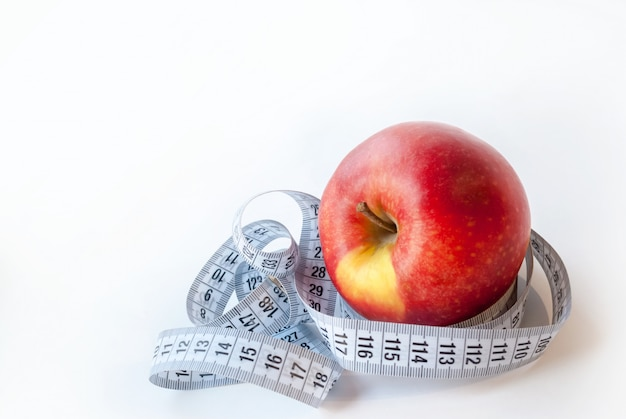 Fresh apple and measuring tape on white background. diet concept. Premium Photo
