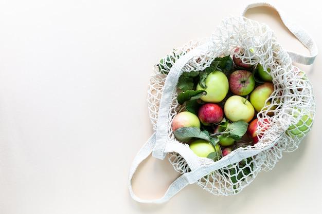 Свежие яблоки в сетке хозяйственной сумки. без отходов, без пластика. здоровое питание и детокс. осенний урожай. плоская планировка, вид сверху. Бесплатные Фотографии