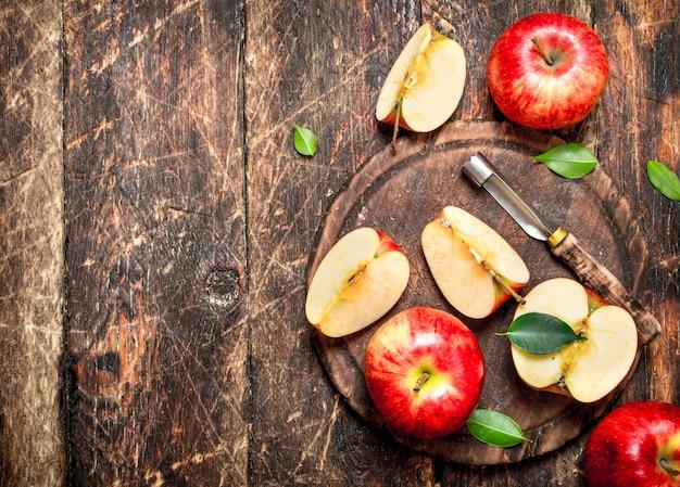 木製のテーブルのまな板に新鮮なリンゴ。 Premium写真