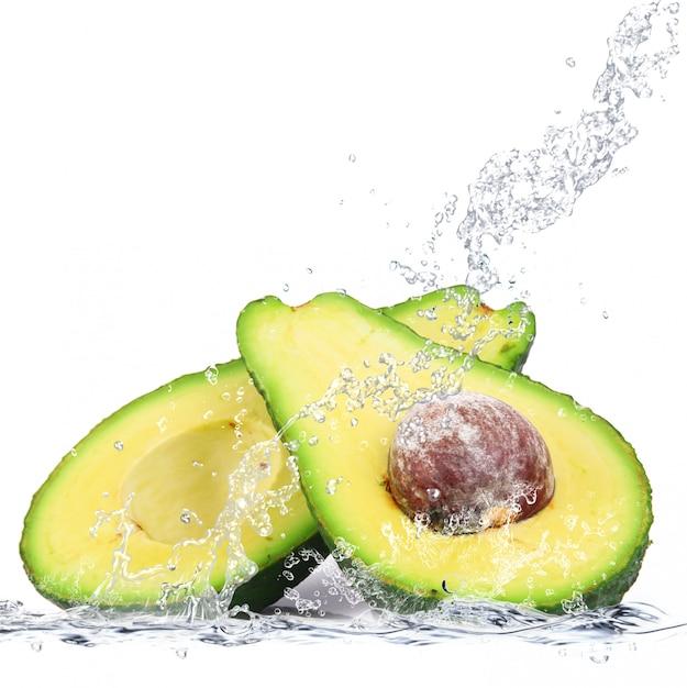 Свежий авокадо падает в воду Premium Фотографии