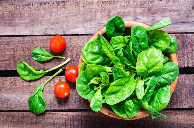 Fresh baby spinach leaves in a bowl and cherry tomatoes on a wooden table Premium Photo