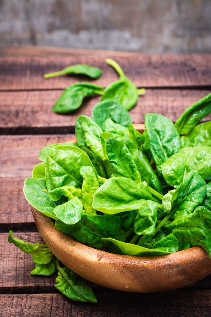 Fresh baby spinach leaves in a bowl on a wooden table. rustic style Premium Photo