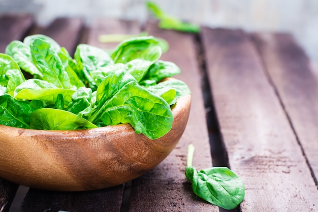 Fresh baby spinach leaves in a bowl on a wooden table Premium Photo