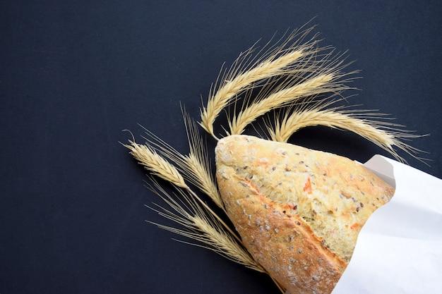 ブラックボードに小麦の穂で焼きたてのパン。ベーカリーやキッチンのコンセプトです。トップビューフラットコピースペースを置きます。 Premium写真