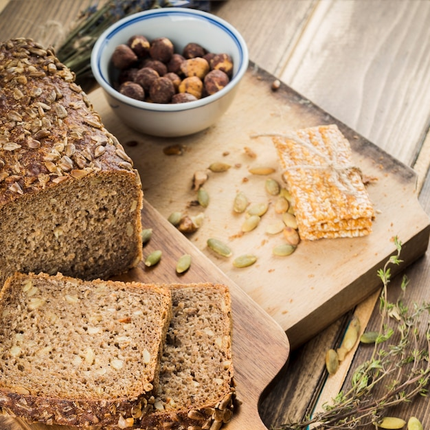 Fresh baked bread with sunflower seeds topping and protein bar on chopping board Free Photo