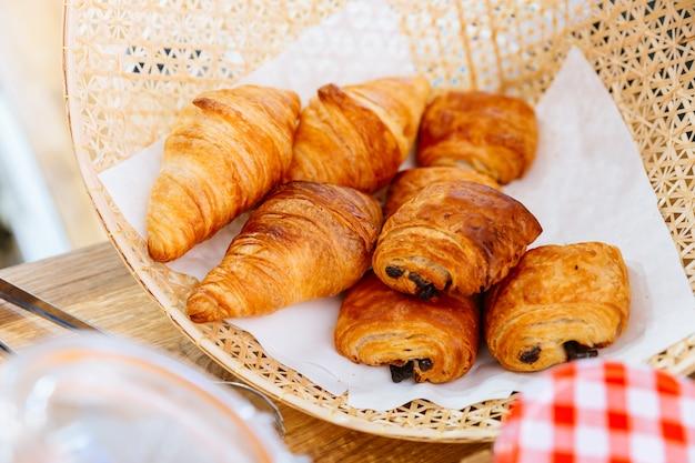 Fresh baked classic butter croissants and raisin croissant inside weaving basket. Premium Photo