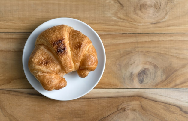 Fresh baked croissants on wood table from above Premium Photo