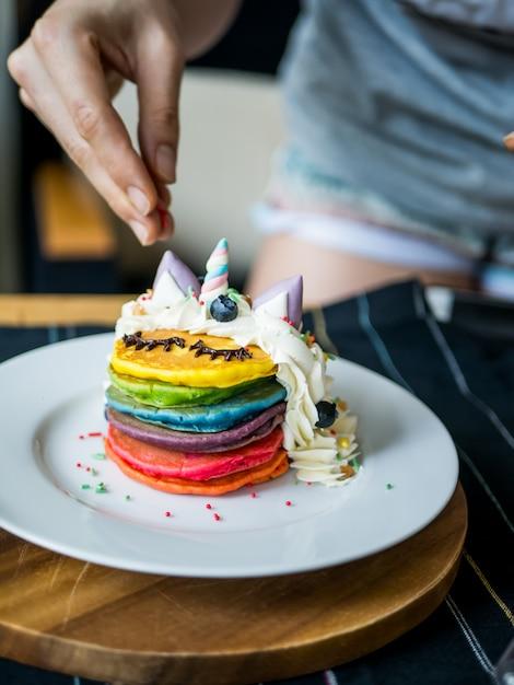 Fresh baked cute unicorn rainbow pancake with. kids meal. Premium Photo