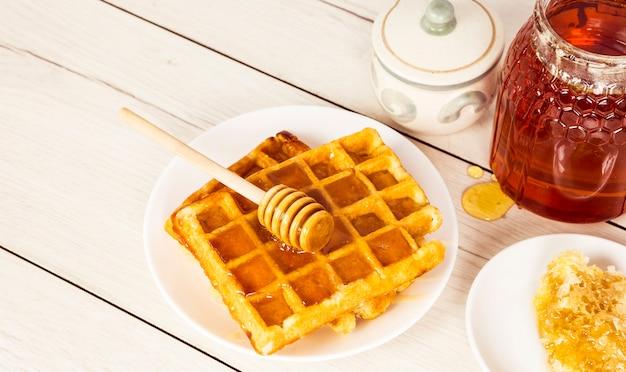木製のテーブルの上に蜂蜜と焼きたてのワッフル 無料写真