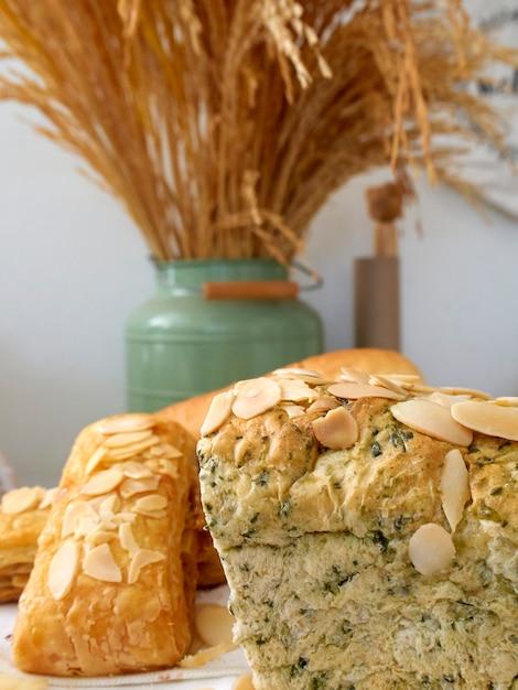 木製トレイと小麦の穀物の新鮮なベーカリー製品、テーブル、白いリネンの上に配置 Premium写真