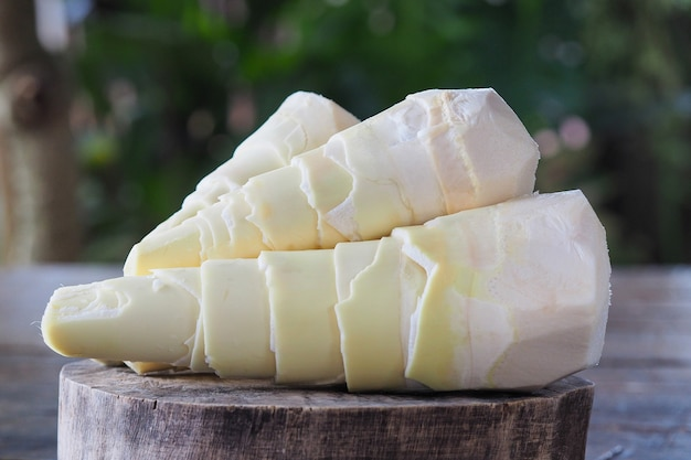 Fresh bamboo shoot on brown chopping wood and green background Premium Photo