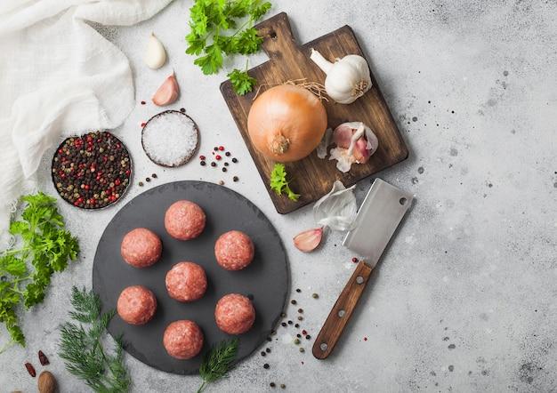 石の上に新鮮な牛肉のミートボール、ペッパー、塩、ニンニク、ディル、パセリ、ディル、玉ねぎ。上面図 Premium写真