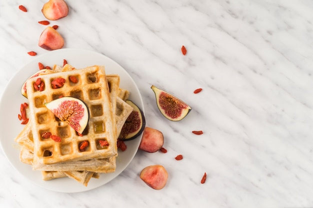 Fresh belgian waffles; and fig served in plate for breakfast Free Photo