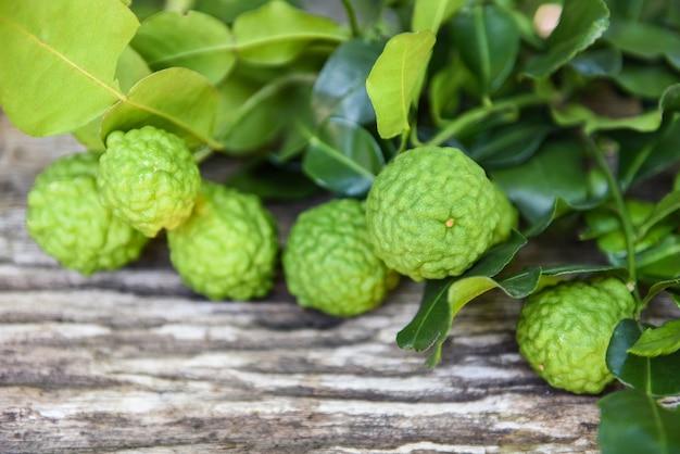 Свежие фрукты бергамота, лайм кафр, цитрусовые бергамия с листьями на деревянных цитрусовых фруктах бергамота Premium Фотографии