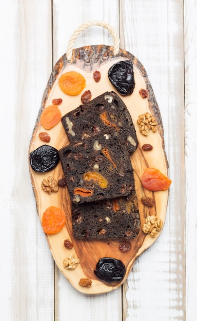 プルーン、ドライアプリコット、クルミ入りの新鮮な黒いデザートパン。 Premium写真