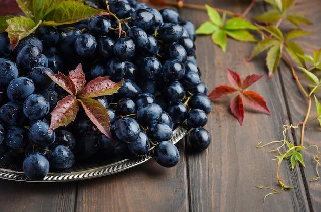 Fresh black grapes on silver plate Premium Photo