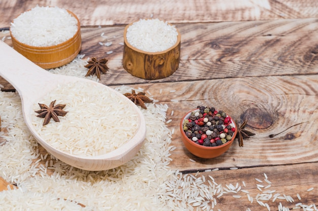 Fresh black pepper and star anise with raw rice over wooden table Free Photo