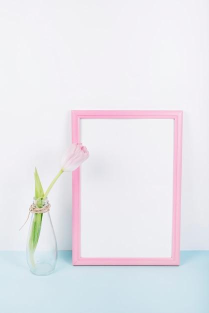ピンクのボーダーフォトフレームと透明な花瓶に新鮮な咲くチューリップの花 Premium写真