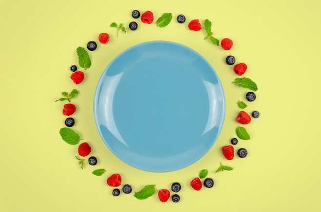 Fresh blueberries, raspberries and mint leaf with blue plate. Premium Photo