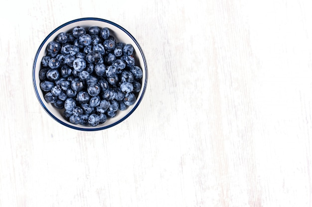 Fresh blueberries in a white bowl on wooden table Premium Photo