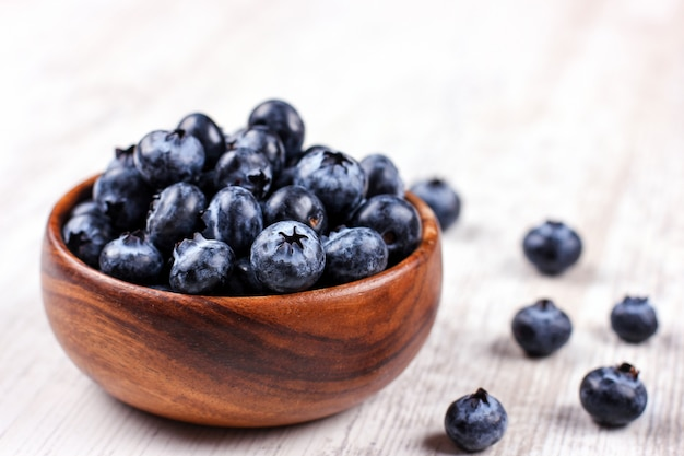 Fresh blueberries in a wooden bowl on white table Premium Photo