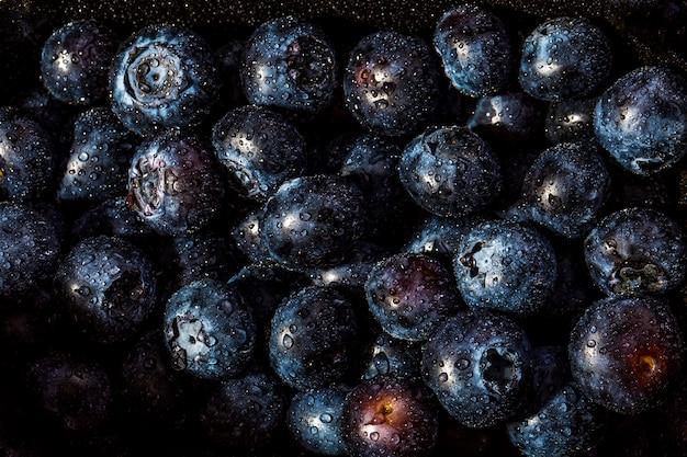 Свежая черника фон. текстура ягоды черники крупным планом с каплями Premium Фотографии