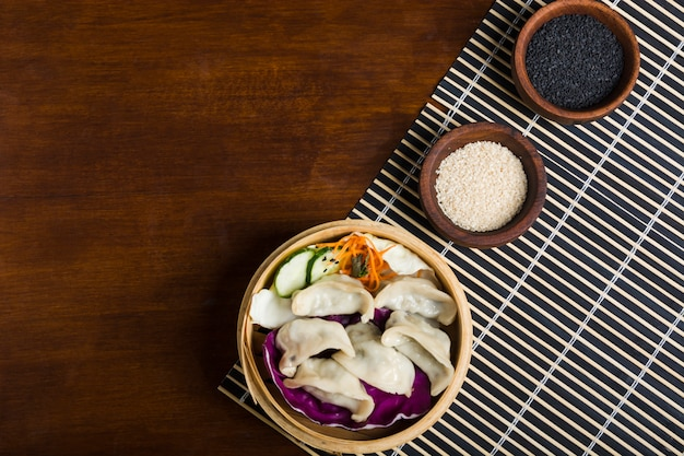 Fresh boiled gyoza dumplings inside the hot steamers with black and white sesame seeds on wooden table Free Photo