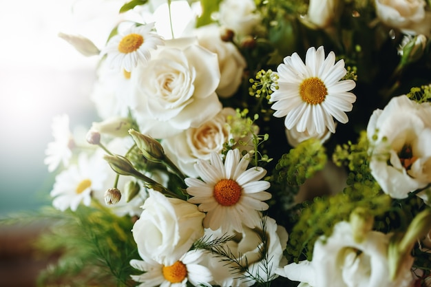 Fresh bouquet of white rose and chamomile close up Premium Photo